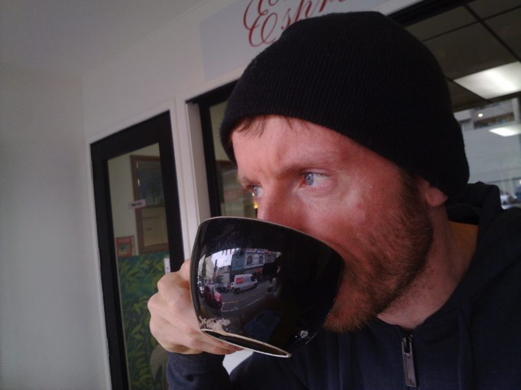 Picture of Nick drinking Coffee from a large black mug